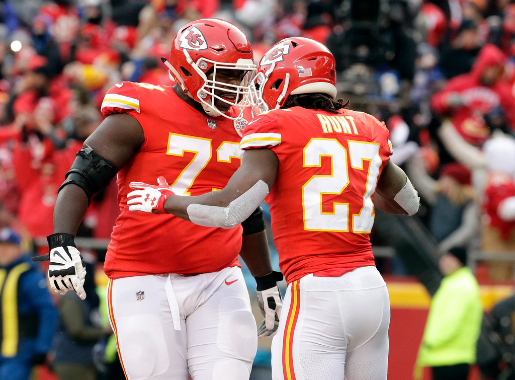 . Kansas City Chiefs running back Kareem Hunt (27) celebrates a touchdown against the Tennessee Titans with offensive lineman Eric Fisher (72) during the first half of an NFL wild-card playoff football game, in Kansas City, Mo., Saturday, Jan. 6, 2018. (AP Photo/Charlie Riedel)