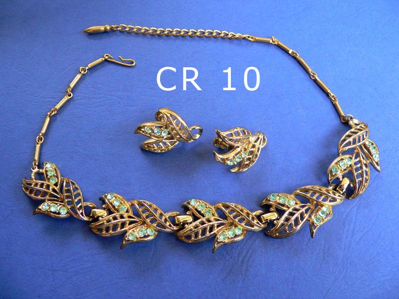 CORO demi-parure composta da girocollo regolabile firmato in uno degli elementi centrali e orecchini a clip metallo color oro scuro e strass color verde chiaro