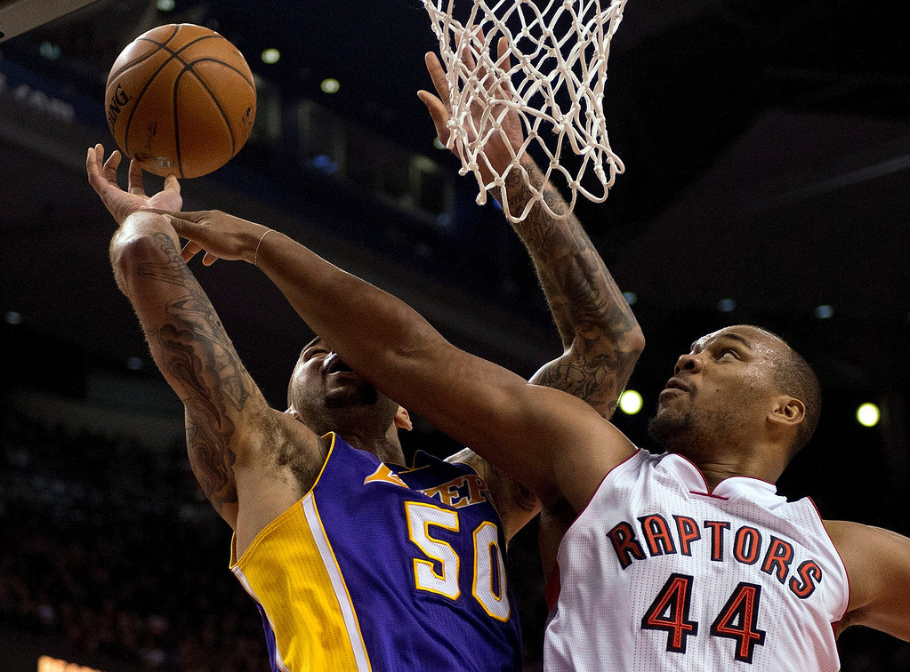 . Toronto Raptors forward Chuck Hayes (44) knocks the ball loose as he defends against Los Angeles Lakers center Robert Sacre (50) during first-half NBA basketball game action in Toronto, Sunday, Jan. 19, 2014. (AP Photo/The Canadian Press, Frank Gunn)