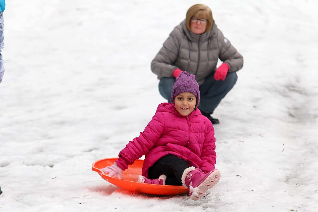. ASophia Bones, 6, does some sledding at the Fitchburg Winterfest at Coggshall Park while her grandmother Michelle Begnoche watches. SENTINEL & ENTERPRISE/JOHN LOVE
