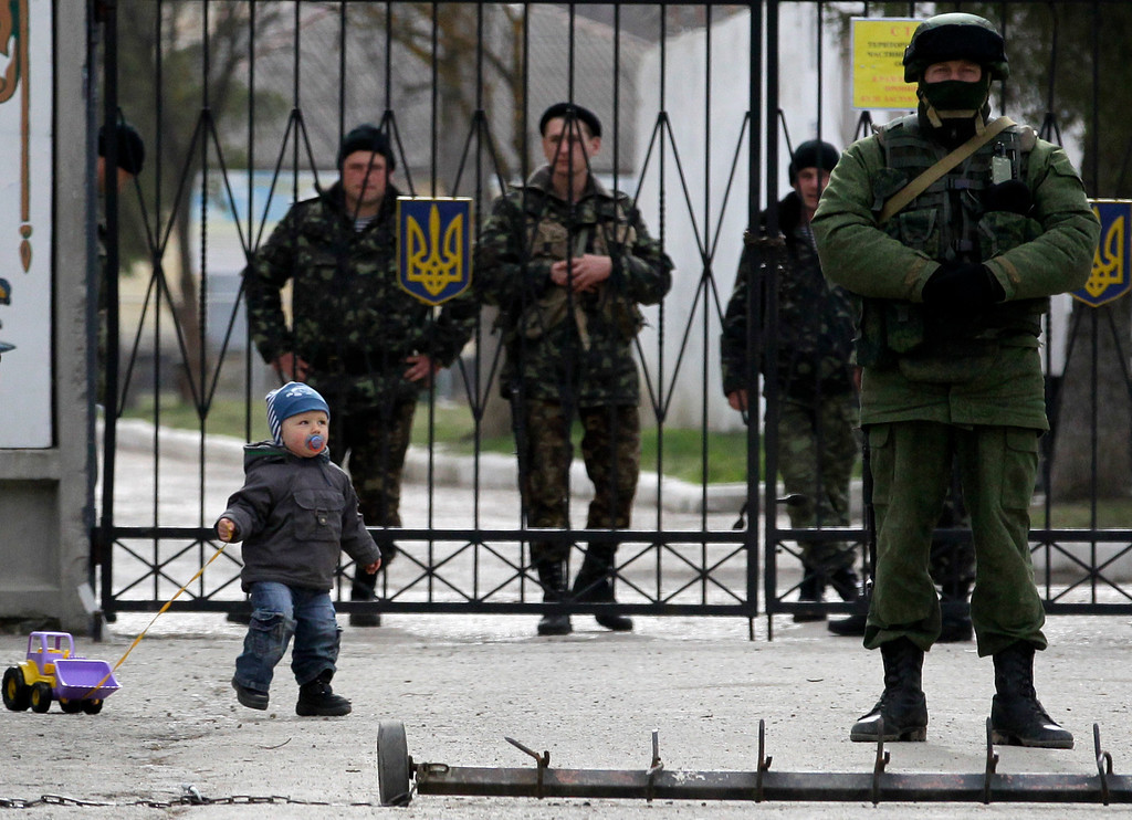 . A child plays near a Russian soldier, right, while Ukrainian soldiers look on from behind gates as the Russian soldier guards the gate of an Ukrainian infantry base in Perevalne, Ukraine, Tuesday, March 4, 2014.  (AP Photo/Darko Vojinovic)