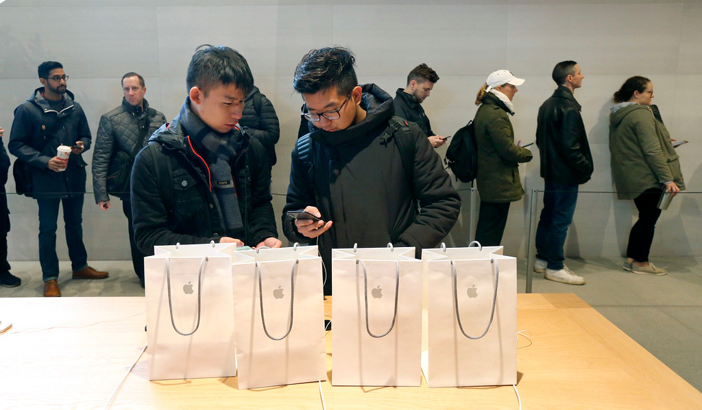. Jiahao Luo, left, and Jiahao Wang, from China, configure one of the four new Apple iPhone X\'s they purchased at the new Apple Michigan Avenue store along the Chicago River Friday, Nov. 3, 2017, in Chicago. (AP Photo/Charles Rex Arbogast)