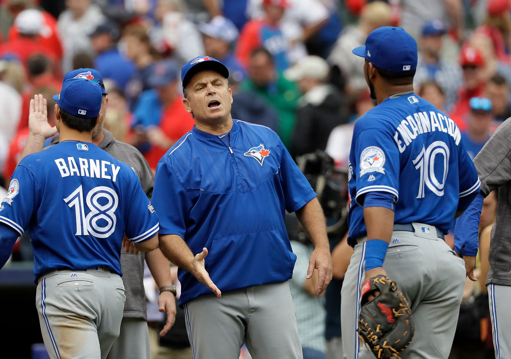 . Toronto Blue Jays manager John Gibbons celebrates their 5-3 win over the Texas Rangers with Darwin Barney (18) and Edwin Encarnacion (10) after Game 2 of baseball\'s American League Division Series, Friday, Oct. 7, 2016, in Arlington, Texas. (AP Photo/David J. Phillip)