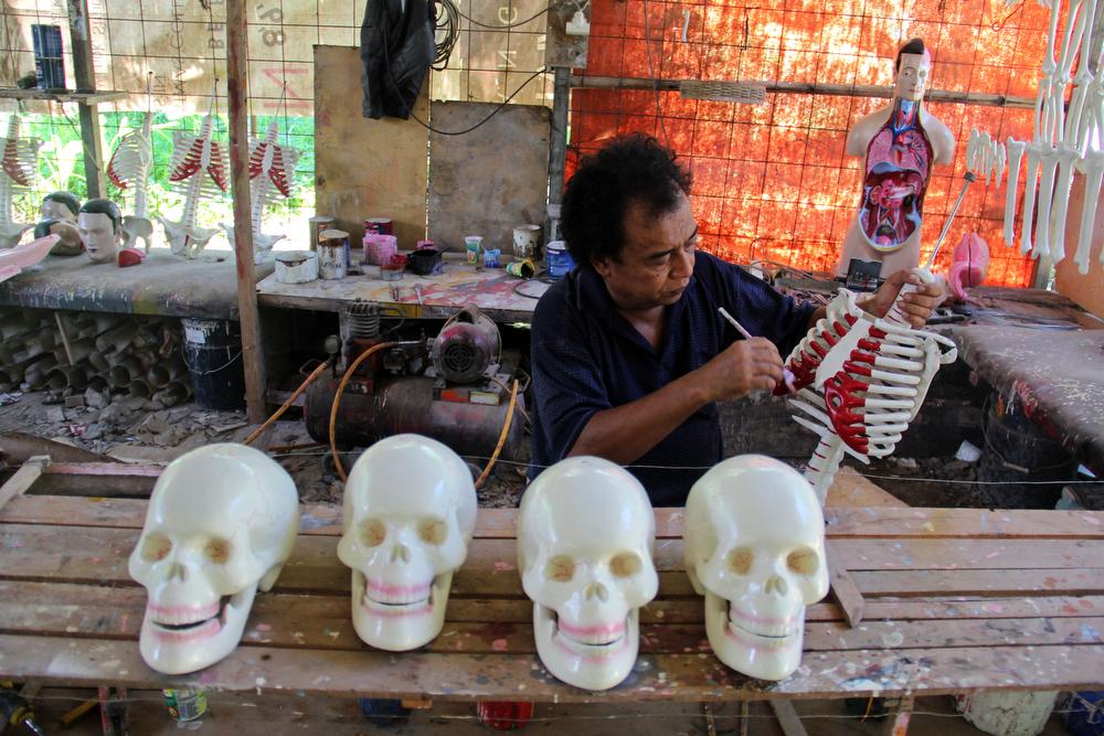 . A craftsman paints human anatomy mannequins on April 23, 2014 in Depok, West Java, Indonesia. The mannequins are made from fiberglass and will be used in schools, hospitals and laboratories.  (Photo by Nurcholis Anhari Lubis/Getty Images)