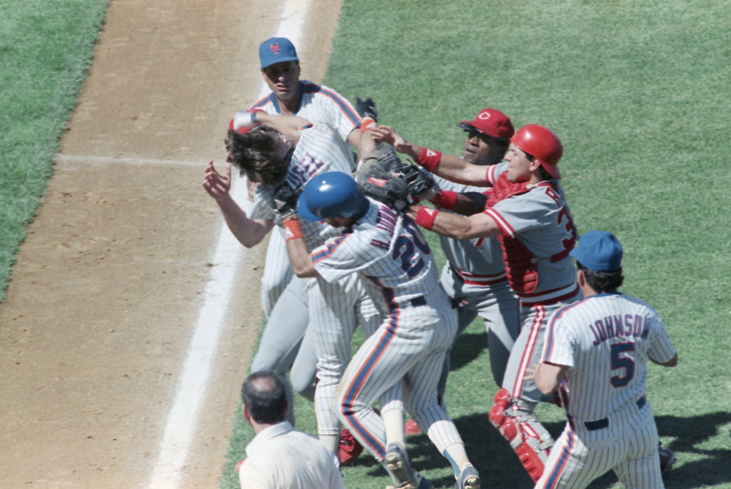 . New York Mets Tim Teufel, left, throws a punch at Cincinnati Reds pitcher Rob Dibble, obscured, as Mets Howard Johnson, foreground, Reds catcher Jeff Reed, right, and third baseman Lenny Harris, right rear, try to separate the two during a bench-clearing brawl game at Shea Stadium, Saturday, July 8, 1989, New York. In background behind Teufel is Mets coach Sam Perlozzo. The Mets won 8-3. (AP Photo/Lou Requena)