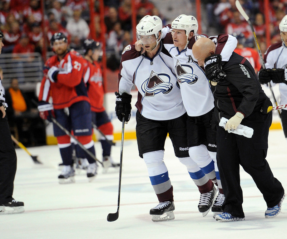 . Colorado Avalanche left wing Cody McLeod, center right, is helped off the ice by a trainer, right, and teammate Jan Hejda, left, during the second period an NHL hockey game against the Washington Capitals, Saturday, Oct. 12, 2013, in Washington. (AP Photo/Nick Wass)