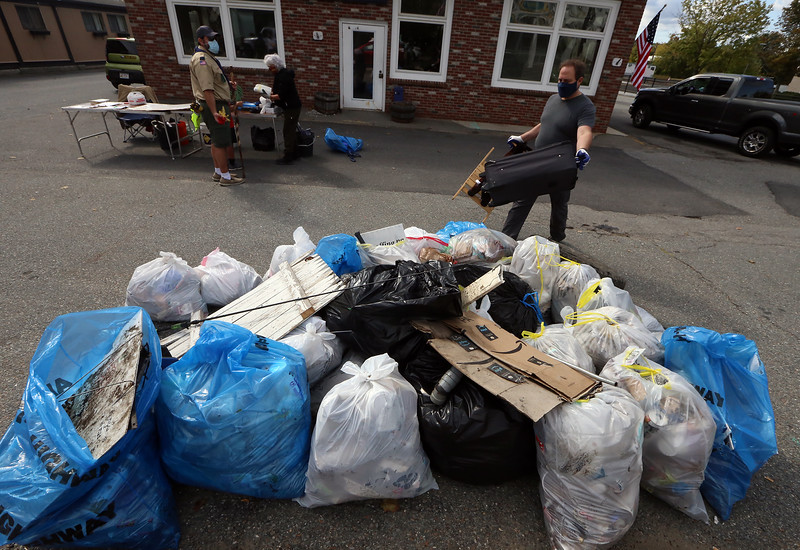 Volunteers pick up litter and trash around Ayer in a town-wide cleanup run by the Ayer Recycling Committee, and part of the Great American Cleanup. Jason Langlais of Ayer, with Scout Pack 32, adds a couple of bulky items to the pile at Depot Square. (SUN/Julia Malakie)