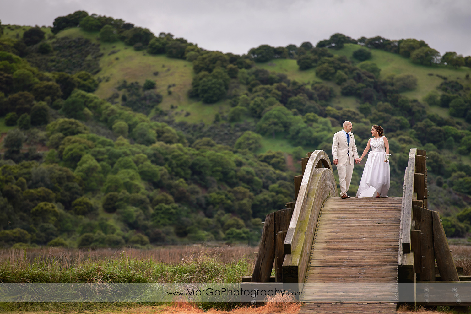 bride and groom walking on the bridge at Martinez Regional Shoreline