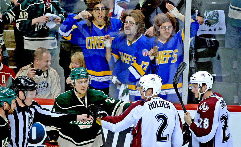""". Minnesota\'s Nino Niederreiter, lower left, gets an assist from fans dressed up as the Hanson Brothers from the movie \""""Slap Shot\"""" during a scuffle with Colorado\'s Nick Holden (#2) and Paul Carey, right, during the first period. (Pioneer Press: Sherri LaRose-Chiglo)"""