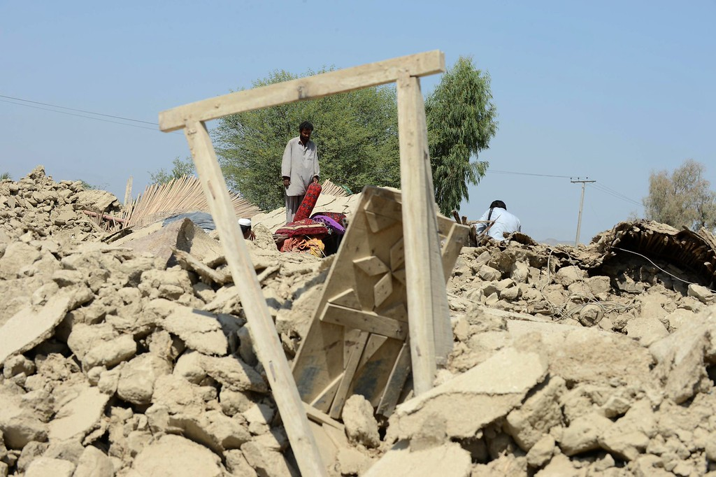 . Pakistani survivors gather around their destroyed houses in the earthquake-devastated district of Awaran on September 25, 2013.    AFP PHOTO/Banaras KHAN/AFP/Getty Images