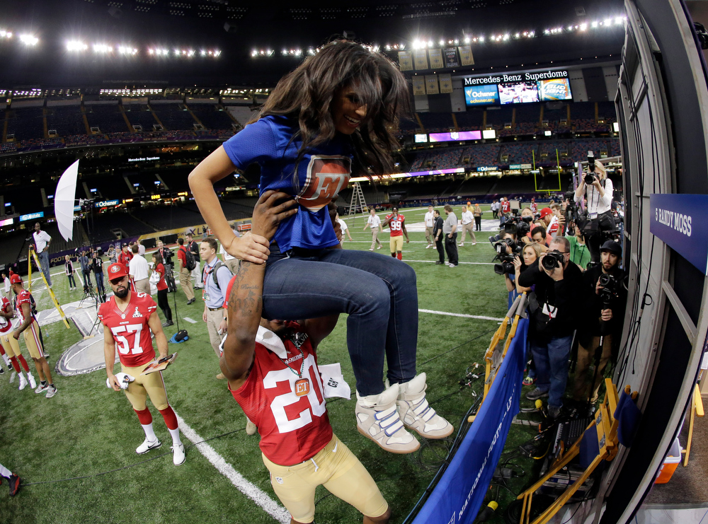 Description of . San Francisco 49ers defensive back Perrish Cox (20) lifts reporter Rosci Diaz during media day for the NFL Super Bowl XLVII football game Tuesday, Jan. 29, 2013, in New Orleans. (AP Photo/Charlie Riedel)