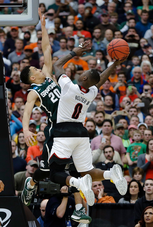 . Michigan State\'s Travis Trice (20) defends Louisville\'s Terry Rozier (0) during the second half of a regional final in the NCAA men\'s college basketball tournament Sunday, March 29, 2015, in Syracuse, N.Y. (AP Photo/Seth Wenig)