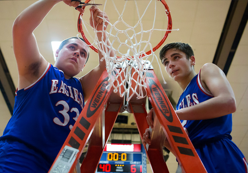 AUGUSTA, Maine -- 02/24/2017 -- Messalonskee's Nicholas Poulliot (left) and Messalonskee's Chase Warren cut pieces of the net down after defeating Oceanside during their Class A boys basketball championship game at the Augusta Civic Center in Augusta Friday. Ashley L. Conti | BDN