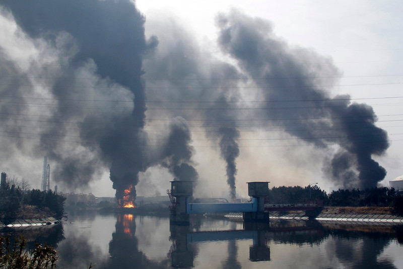 . Smoke rise from an oil refinery on fire following a tsunami triggered by a strong earthquake in Tagajo, Miyagi Prefecture, northern Japan, Sunday, March 13, 2011. (AP Photo/Koji Sasahara)
