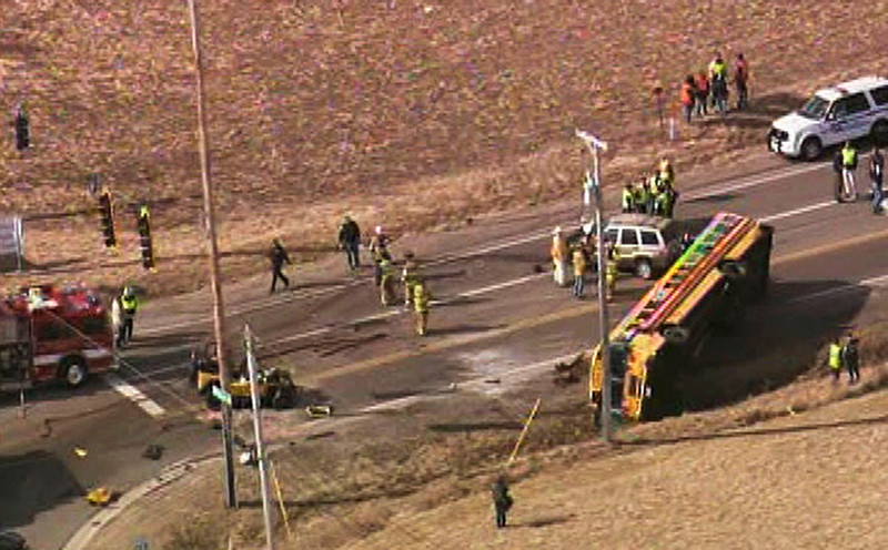 . Emergency personnel work the scene where a school bus overturned that was carrying about two dozen elementary school children Friday, April 5, 2013, near Wadsworh, Ill. Television footage from the scene shows the bus on its side, with two mangled cars nearby. Authorities say one person died and more than three dozen people are injured, including elementary school children. Everyone aboard the bus survived. (AP Photo/Courtesy of NBCCHicago.com)