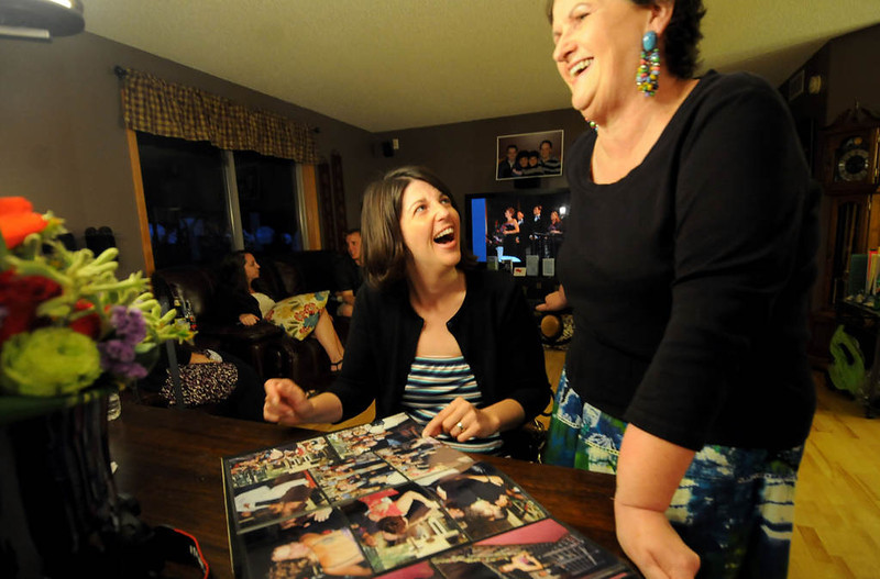 . Becca Schroeder, left, share a laugh with her mother Jean Hayenga, as they look at photos of Ryan Pfeifle and Bradley Weber wedding 10 years ago that they both attended on July 26, 2003. (Pioneer Press: Sherri LaRose-Chiglo)