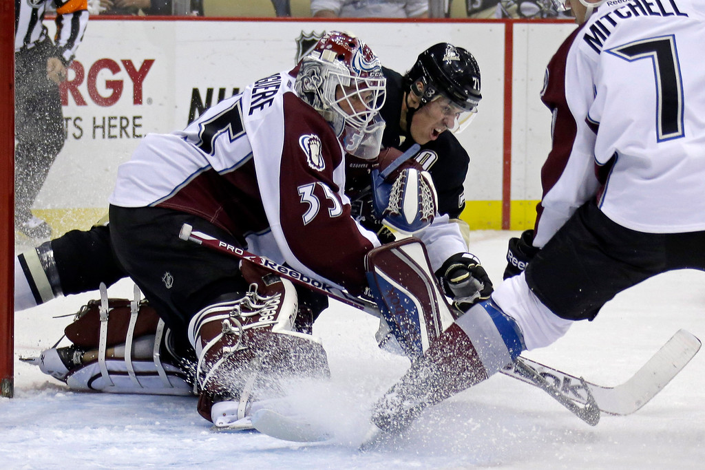 . Pittsburgh Penguins\'  Evgeni Malkin (71) collides with Colorado Avalanche goalie Jean-Sebastien Giguere (35) after getting of a shot in the second period of an NHL hockey game in Pittsburgh Monday, Oct. 21, 2013.  (AP Photo/Gene J. Puskar)