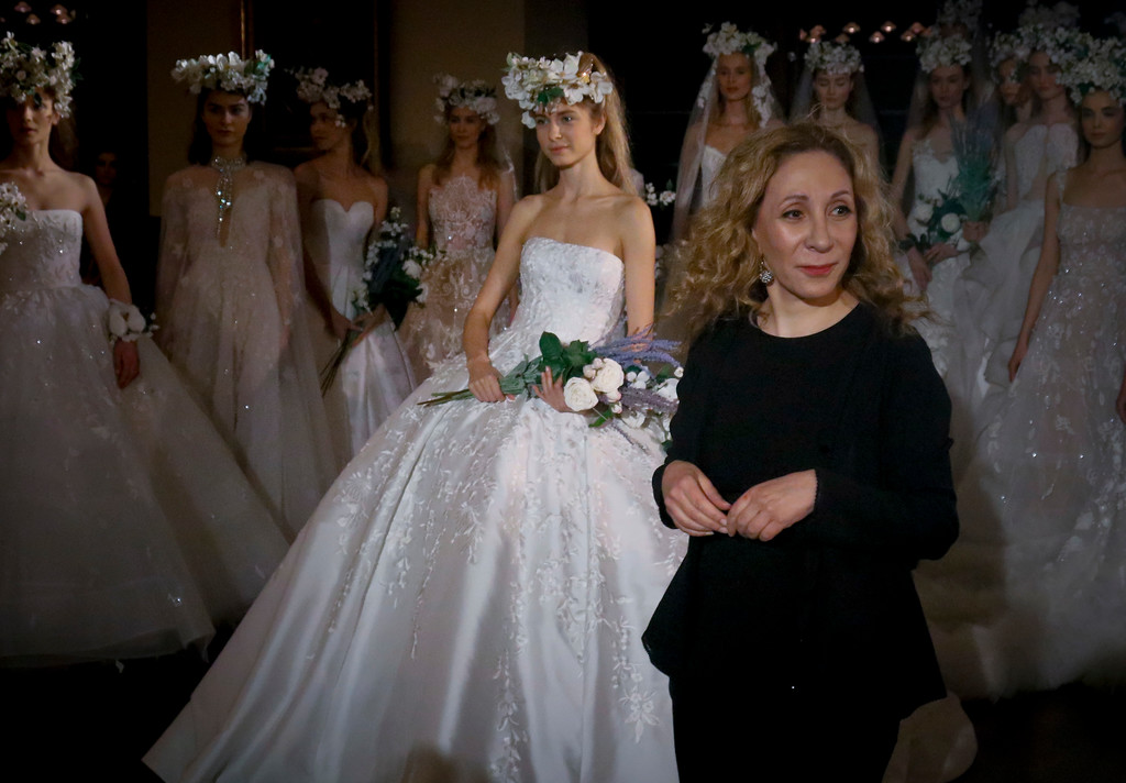 . Fashion designer Reem Acra, center, join models after showing her latest bridal collection, during Bridal Fashion Week, Thursday April 12, 2018 in New York. (AP Photo/Bebeto Matthews)