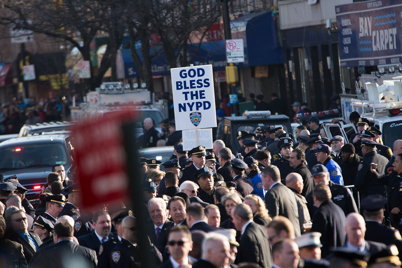 ". A sign is posted that reads ""God Bless The NYPD\"" as police officers gather outside the funeral of slain New York Police Department (NYPD) officer Rafael Ramos at the Christ Tabernacle Church on December 27, 2014 in the Glenwood section of the Queens borough of New York City. Ramos was shot, along with Police Officer Wenjian Liu while sitting in their patrol car in an ambush attack in Brooklyn on December 20. Thousands of fellow officers, family, friends and Vice President Joseph Biden arrived at the church for the funeral.  (Photo by Kevin Hagen/Getty Images)"