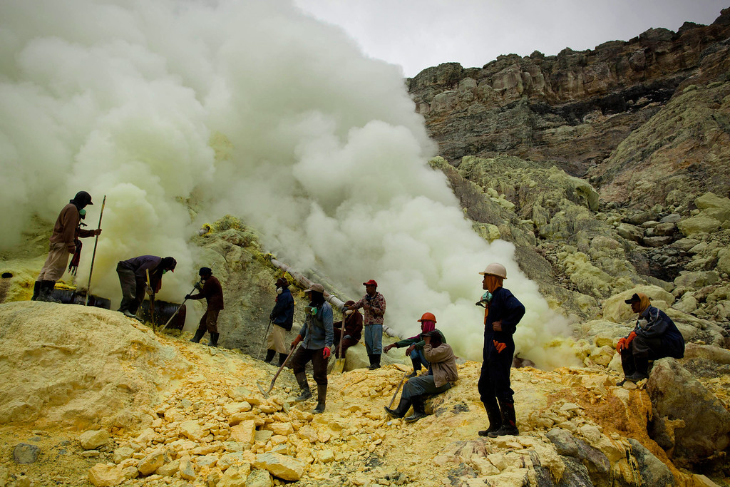 . Miners uses poles to extract sulphur from pipes at the flow crater during an annual offering ceremony on the Ijen volcano on December 17, 2013 in Yogyakarta, Indonesia. (Photo by Ulet Ifansasti/Getty Images)