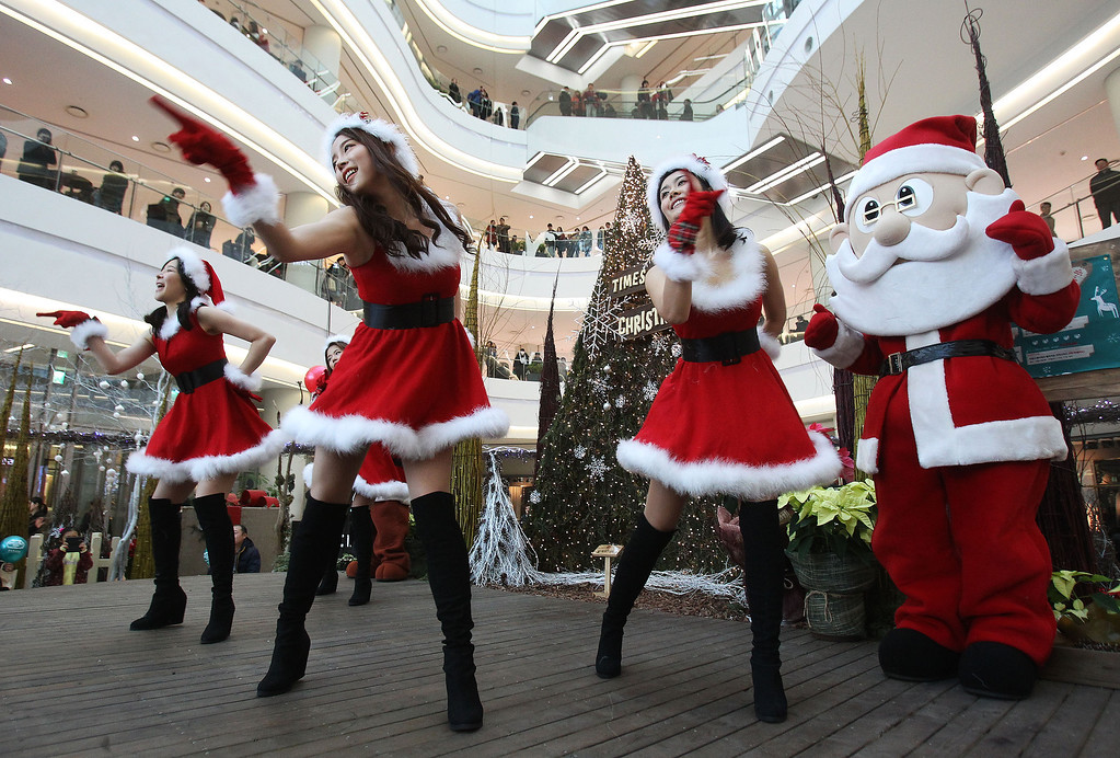 . Employees dressed as Santa Claus perform as part of a shopping mall\'s Christmas celebrations in Seoul, South Korea, Tuesday, Dec. 24, 2013.  A lot of South Korean companies take advantage of the Christmas to promote their business amid weak sales and economic slowdown. (AP Photo/Ahn Young-joon)
