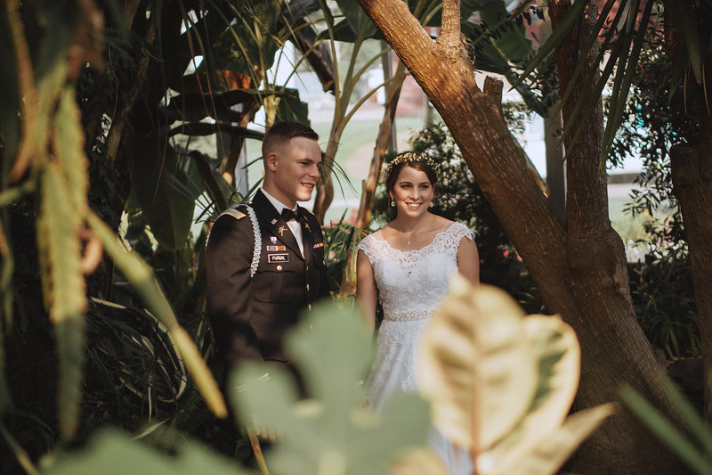 In the greenhouse, the bride and groom stand next to each other and smile.