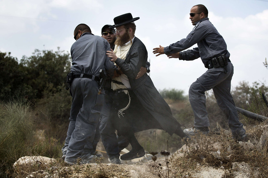 . An Ultra-Orthodox Jewish man is arrested by Israeli policemen in Ramat Beit Shemesh West of Jerusalem on August 12 2013, after dozens of Haredim protest against desecration of ancient graves were discovered at a new housing construction site. Some 14 Ultra-orthodox Jews were arrested.   MENAHEM KAHANA/AFP/Getty Images