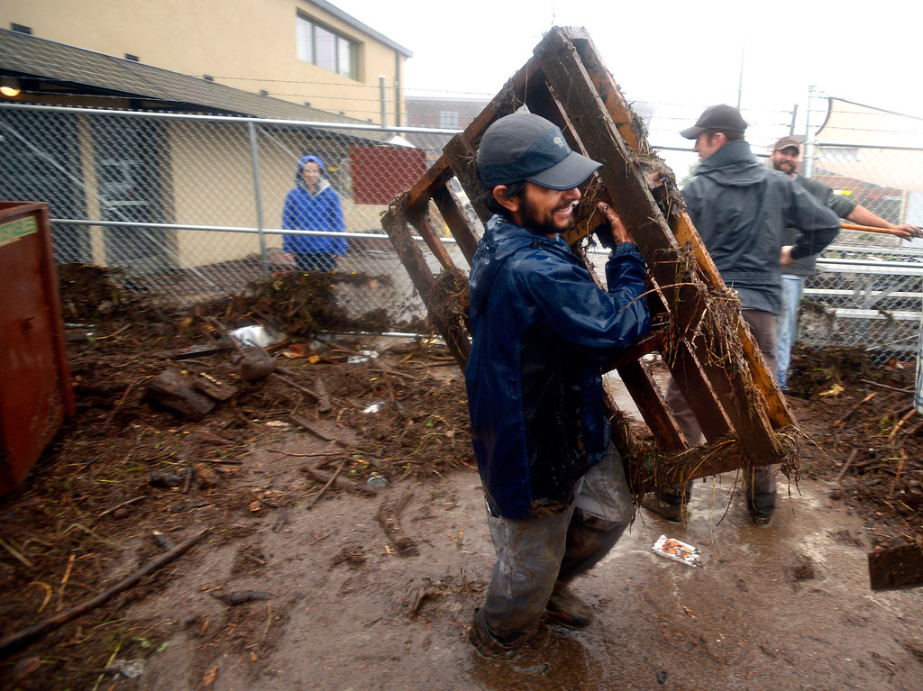 . Jason Ortiz with Namaste Solar , carriers debris from behind the business as his coworkers clean up after the flood in North Boulder, Colo., on  Thursday, Sept.  12, 2013.  Heavy rains and scarring from recent wildfires sent walls of water crashing down mountainsides early Thursday in Colorado, cutting off mountain towns.  Boulder County was hit hardest, but flooding was reported all along the Front Range, from Colorado Springs to north of Fort Collins. (AP Photo/The Daily Camera, Paul Aiken) NO SALES