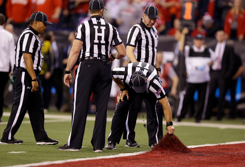 . Officials examine a problem with the artificial turf during the second half of the Big Ten championship NCAA college football game between Ohio State and Wisconsin, Saturday, Dec. 2, 2017, in Indianapolis. (AP Photo/Michael Conroy)