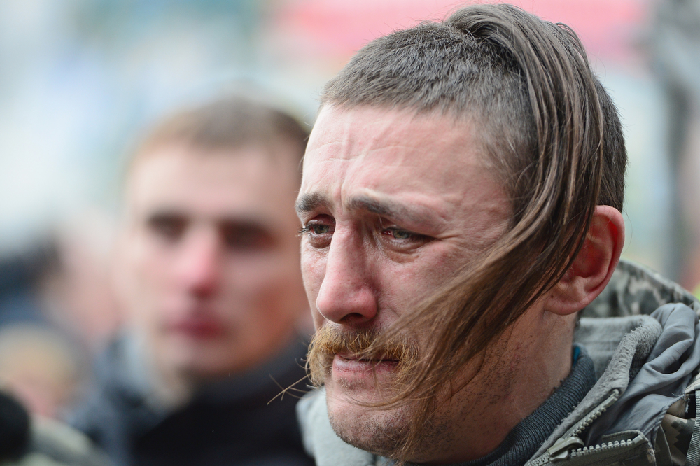 . A man looks emotional as he watches the coffin of a dead anti-government demonstrator killed in clashes with police is carried through the crowd in Independence square February 22, 2014 in Kiev, Ukraine. The offices of Ukrainian President Viktor Yanukovych have been left unguarded, with the protesters in full control of the streets surrounding the government district. The opposition have called for elections to take place on May 25 and demanded that President Yanukovych stand down immediately.  (Photo by Jeff J Mitchell/Getty Images)