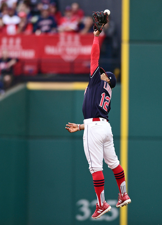 . Cleveland Indians\' Francisco Lindor reaches but can\'t catch a single hit by New York Yankees\' Todd Frazier in the second inning of Game 2 of baseball\'s American League Division Series, Friday, Oct. 6, 2017, in Cleveland. (AP Photo/David Dermer)