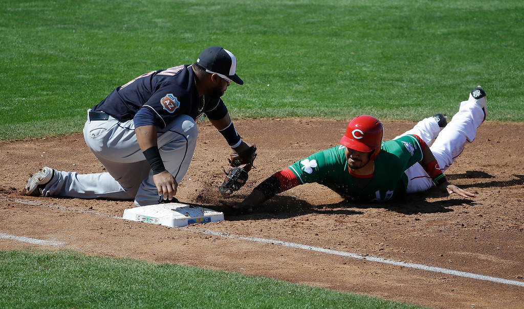 . Cincinnati Reds\' Eugenio Suarez, right, dives safely back to first as Cleveland Indians\' Carlos Santana applies the tag during the third inning of a spring training baseball game on Thursday, March 17, 2016, in Goodyear, Ariz. (AP Photo/Darron Cummings)