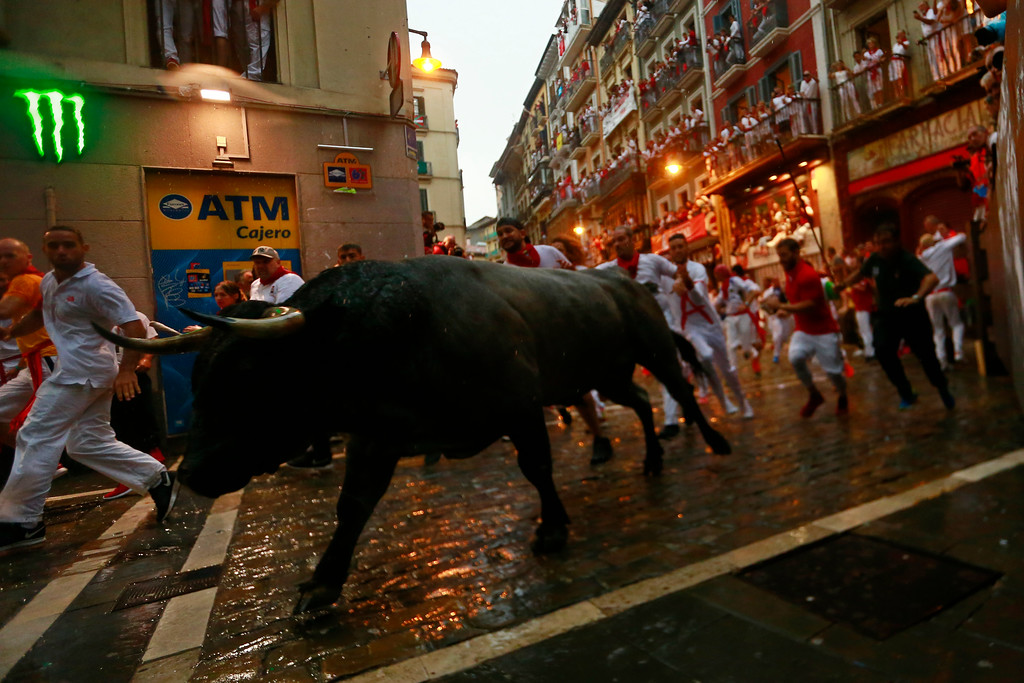 . Revellers run next to a fighting bull from the Jose Escolar ranch during the second day of the running of the bulls at the San Fermin Festival in Pamplona, northern Spain, Sunday, July 8, 2018. Revellers from around the world flock to Pamplona every year to take part in the eight days of the running of the bulls. (AP Photo/Alvaro Barrientos)