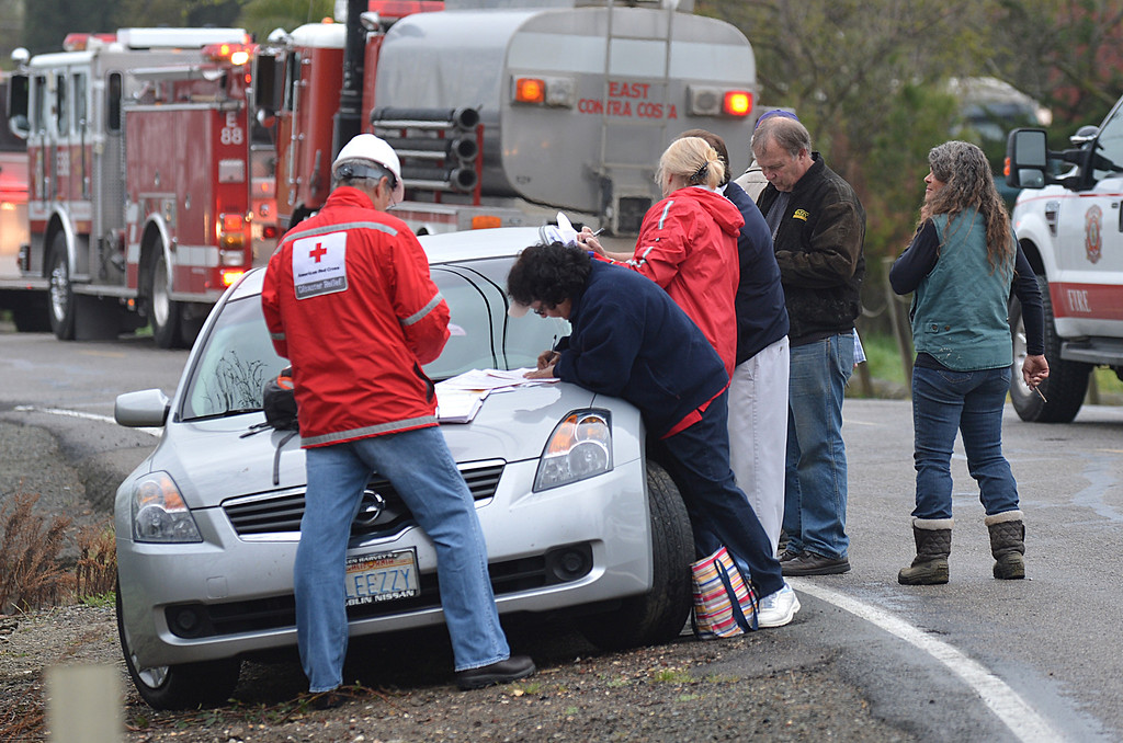 . Red Cross volunteers help a group of neighbors that were affected by a two-alarm fire on Taylor Road in Bethel Island, Calif., on Wednesday, March 20, 2013. The blaze destroyed two homes and damaged a third. (Dan Rosenstrauch/Staff)
