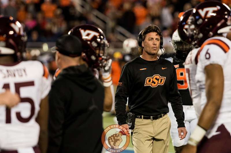 Mike Gundy checks on an injured player during the Camping World Bowl between Virginia Tech and Oklahoma State in Orlando, Fl., Thursday, Dec. 28, 2017. (Special by Cory Hancock)