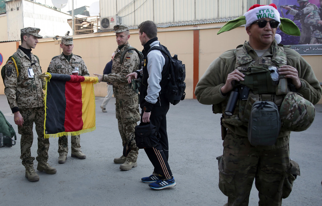 . A German soldier roles their flag before a soccer match with British soldier\'s team during Christmas day in Resolute Support HQ, in Kabul, Afghanistan, Sunday, Dec. 25, 2016. NATO soldiers, Resolute Support mission played a soccer match marking the 102 years anniversary of WW1 in Kabul. The match ended up with British winning the match by (1-0). (AP Photos/Massoud Hossaini)