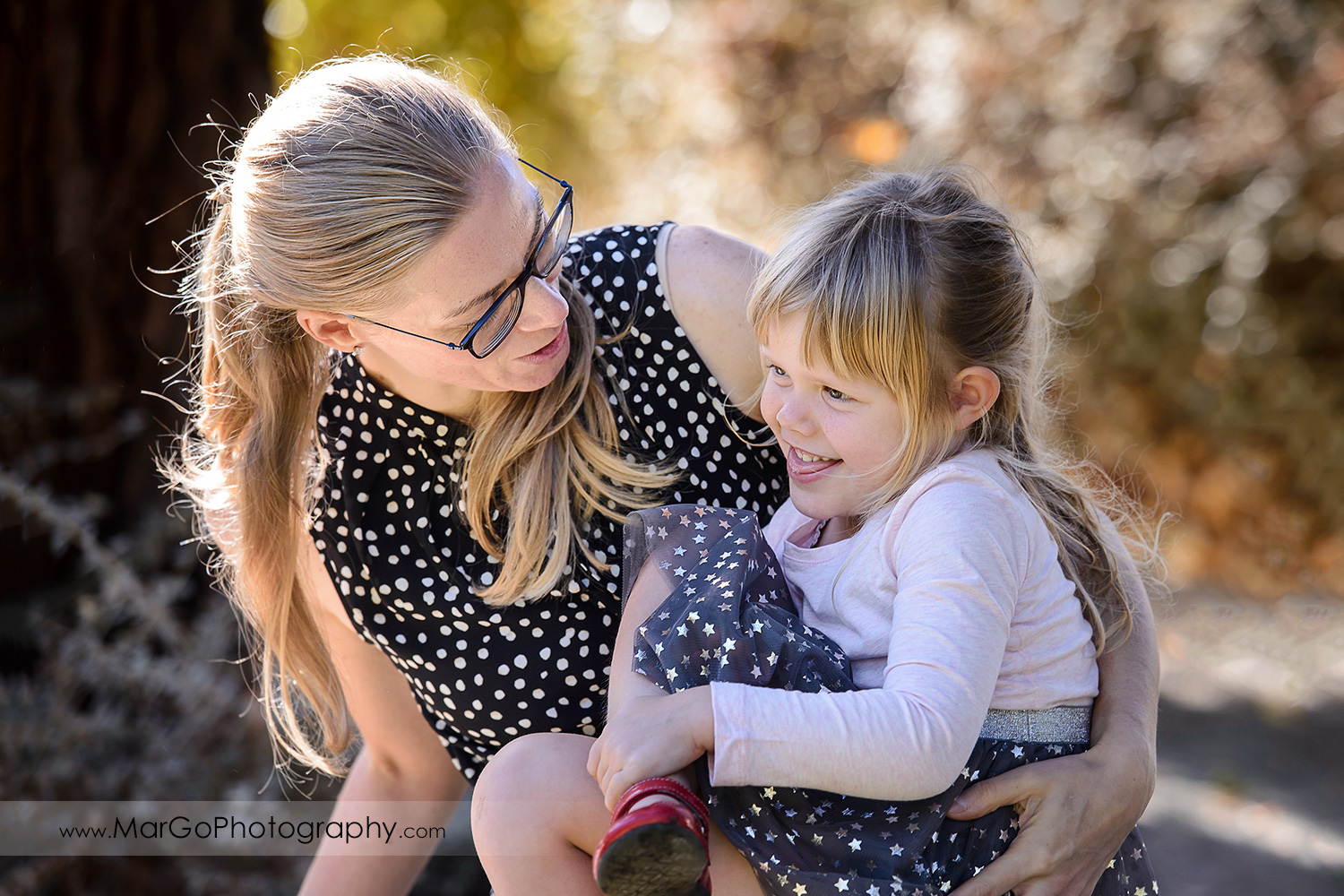 portarit of woman in black dress with white dots and little girl in navy blue skirt with golden stars at Mountain View Shoreline Lake Park