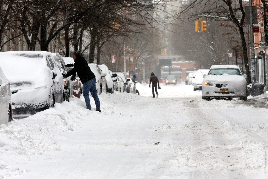 . A man scrapes snow from his car on the Lower East side neighborhood of Manhattan, Tuesday, Jan. 27, 2015. A storm packing blizzard conditions spun up the East Coast early Tuesday, pounding coastal eastern Long Island into Maine with high winds and heavy snow.   (AP Photo/Mary Altaffer)
