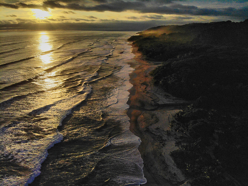 Sunset over a Lush Tropical Beach Paradise with blue water, great waves and rock formations in Malpais / Santa Teresa, Nicoya Peninsula Costa Rica