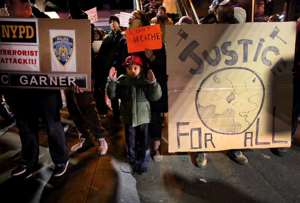 . Raisa Valerio, 23, and her son, Tyler Valerio, 5, join a group on E. 125th St. during a protest December 4, 2014 in New York City. Protests began after a Grand Jury decided to not indict officer Daniel Pantaleo. Eric Garner died after being put in a chokehold by Pantaleo on July 17, 2014. Pantaleo had suspected Garner of selling untaxed cigarettes. (Photo by Yana Paskova)