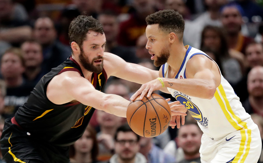 . Golden State Warriors\' Stephen Curry, right, drives against Cleveland Cavaliers\' Kevin Love in the first half of an NBA basketball game, Monday, Jan. 15, 2018, in Cleveland. (AP Photo/Tony Dejak)