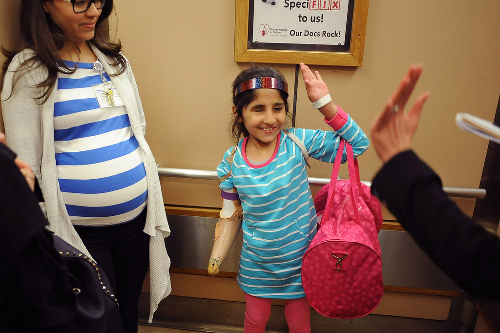 . Shah Bibi, 7, of Afghanistan offers up a high five following her occupational therapy appointment for her new prosthetic arm Wednesday at Shriners Hospital for Children in Los Angeles, CA. Bibi lost most of her right arm and the use of an eye after picking up a hand grenade.  She was brought to Southern California for medical treatment in December by the Children of War Foundation and is set to return to her remote Afghani village next week.(Andy Holzman/Los Angeles Daily News)