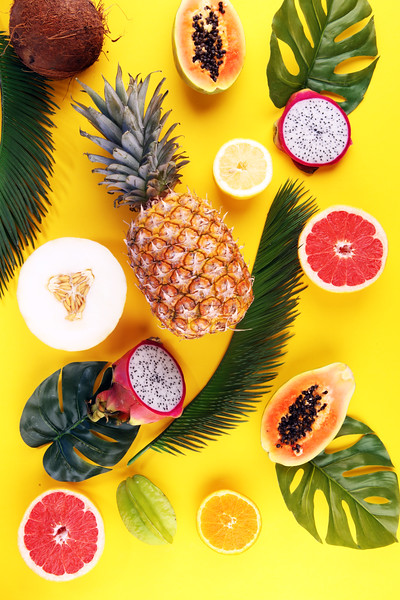 Exotic Fruits And Tropical Palm Leaves On Pastel Yellow Background - Papaya, Mango, Pineapple, Banan