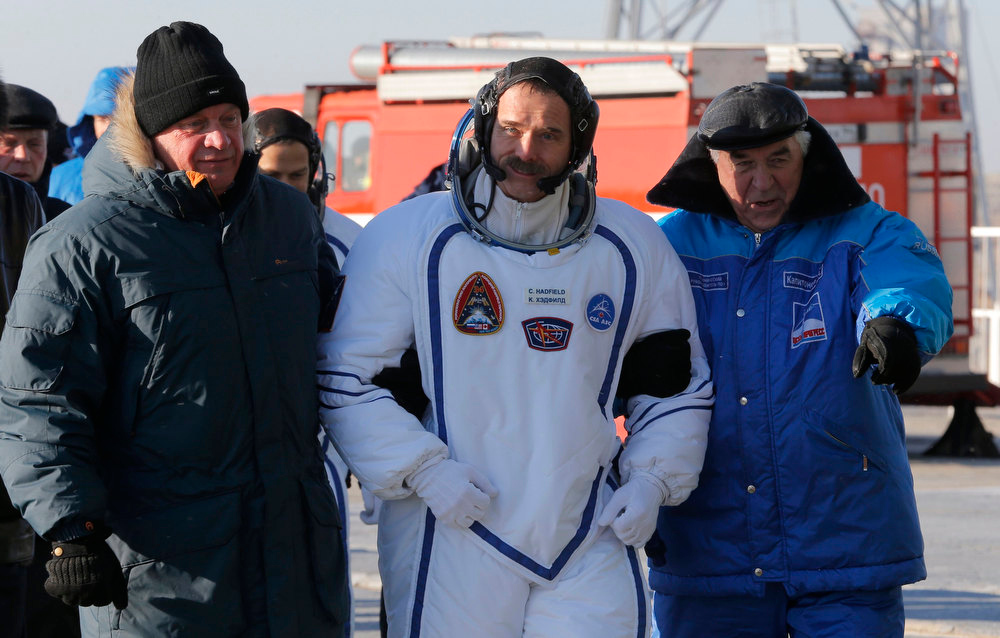 Description of . International Space Station crew member Canadian astronaut Chris Hadfield (C) walks before boarding the Soyuz TMA-07M spacecraft at the Baikonur cosmodrome December 19, 2012.  REUTERS/Dmitry Lovetsky/Pool