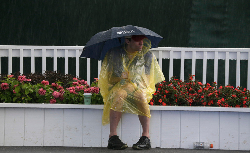 . A spectator waits out a weather delay during the first round of the U.S. Open golf tournament at Merion Golf Club, Thursday, June 13, 2013, in Ardmore, Pa. (AP Photo/Gene J. Puskar)