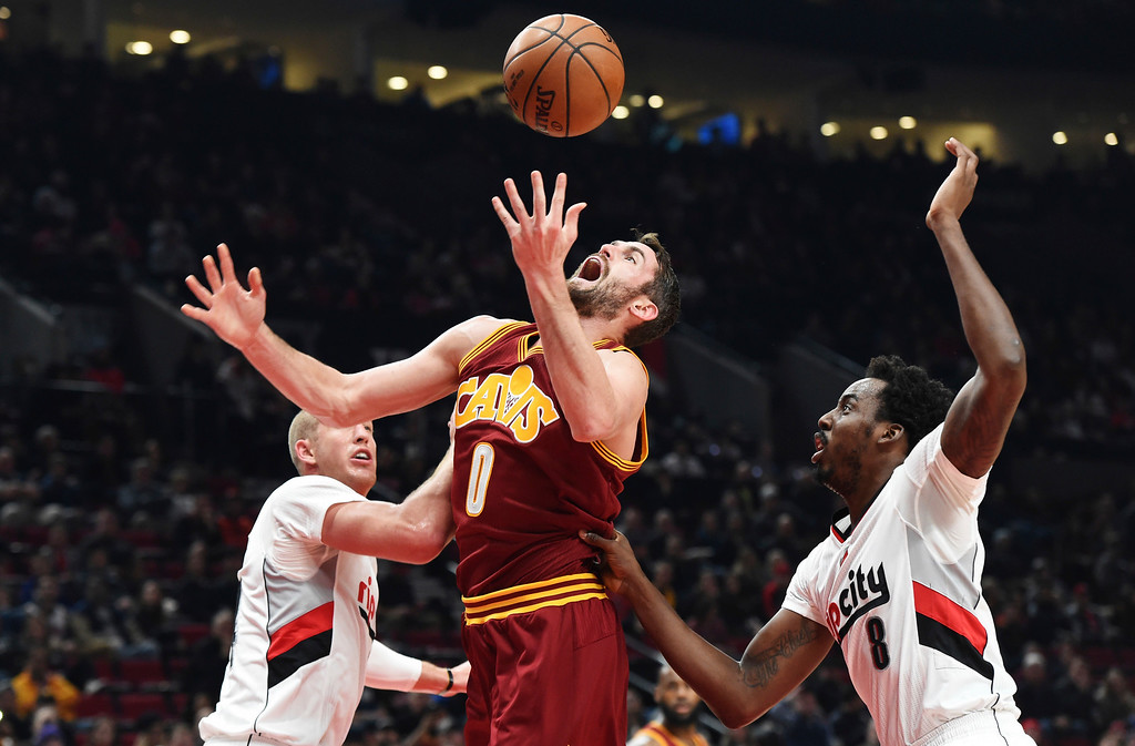 . Cleveland Cavaliers forward Kevin Love battles for a rebound with Portland Trail Blazers center Mason Plumlee and forward Al-Farouq Aminu during the first half of an NBA basketball game in Portland, Ore., Wednesday, January 11, 2017. (AP Photo/Steve Dykes)