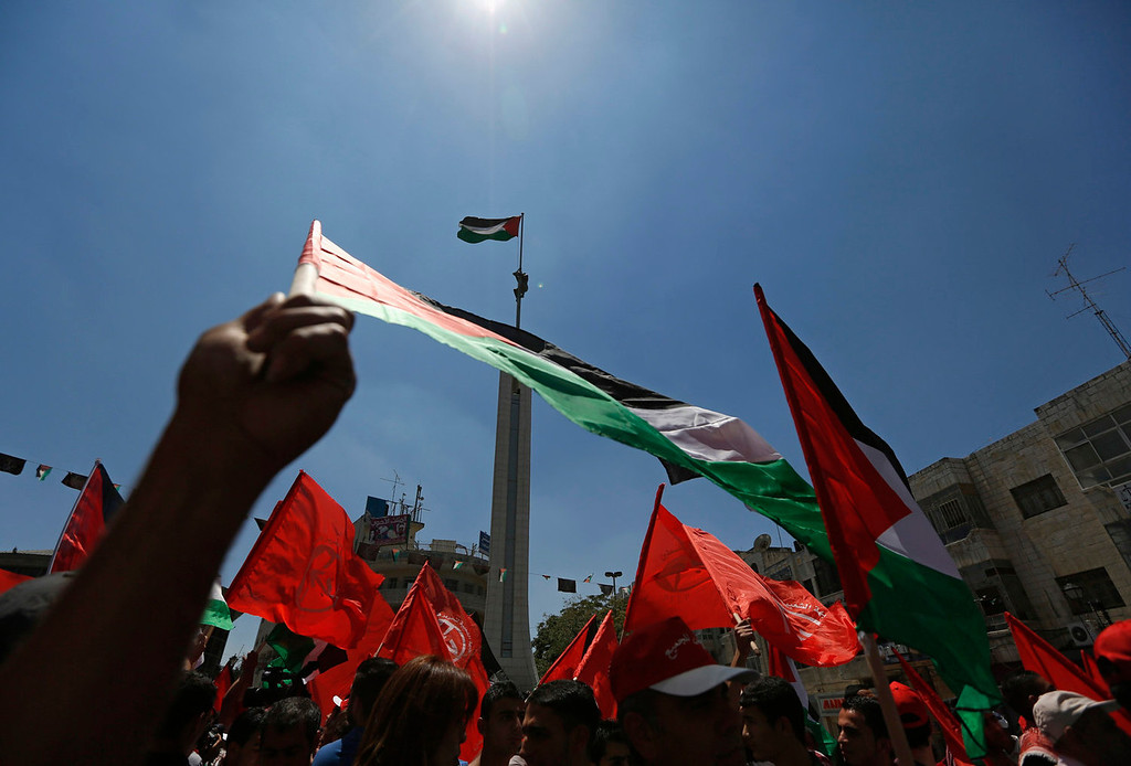 . Palestinians wave Palestinian and Popular Front for the Liberation of Palestine (PFLP) flags during a protest against the renewal stalled peace talks with Israel, in the West Bank city of Ramallah July 28, 2013. Israel was expected on Sunday to approve releasing more than 100 Arab prisoners as a step to renew stalled peace talks with the Palestinians ahead of plans to convene negotiators in Washington later this week.   REUTERS/Mohamad Torokman
