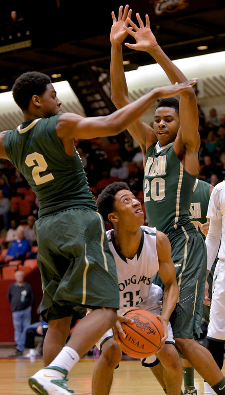 . Jeff Forman/JForman@News-Herald.com Ryan Russell looks to shoot between Irish defenders Johnnie Roinson and Henry Baddley during the first half of the Cougars\' 68-52 Division II regional semifinal loss March 13 to St. Vincent St. Mary at the Canton Civic Center.