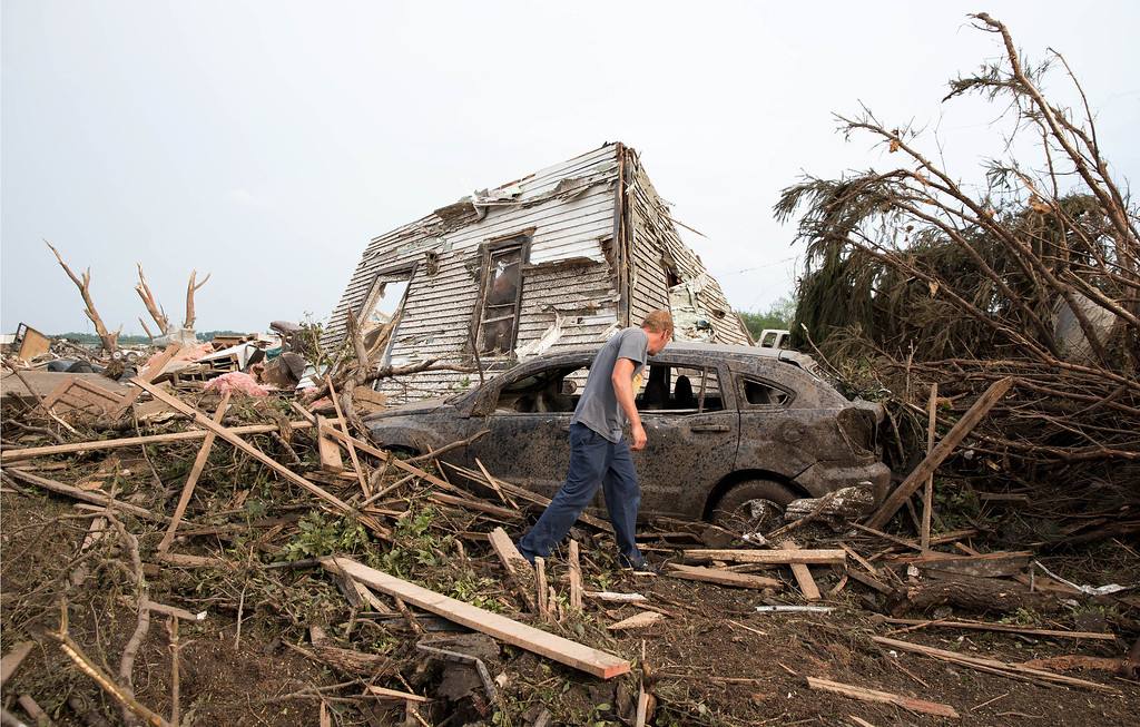 . Tim Nelson  searches for survivors in Pilger, Neb.,  after the town was hit by a tornado Monday June 16, 2014.  Ast least one person has died due to the storm.  (AP Photo/The Omaha World-Herald/Ryan Soderlin)