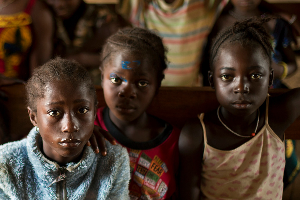 . In this photo taken Thursday, Nov. 20, 2014, children listen to the village chief in the communal room in the Guinean village of Meliandou, some 400 miles (600 mms) south-east of Conakry, Guinea, believed to be Ebola\'s ground zero. Meliandou, a small village at the top of a forested hill reached by a rutted red earth track, is notorious as the birthplace and crucible of the most deadly incarnation of the Ebola virus to date. Today villagers here are in debt, stigmatized, hungry and still angry and deeply suspicious about who or what brought the disease that has devastated their lives. (AP Photo/Jerome Delay)